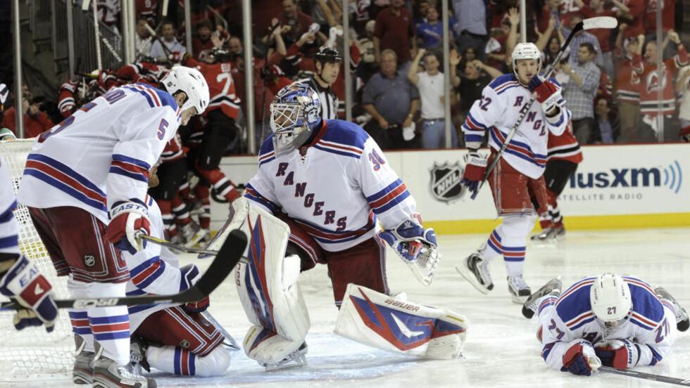 ISKALDT: New York Rangers-spillerne depper mens New Jersey Devils feirer vinnermålet i bakgrunnen. Foto: SCANPIX/REUTERS/Ray Stubblebine