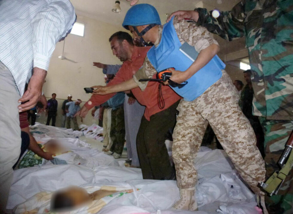 MASSAKRE: En FN-observatør dokumenterer døde etter massakren i Houla. Foto: Reuters/Shaam News/Scanpix