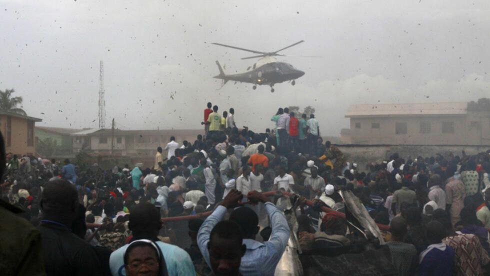 SKUELYSTENE:  Flyvraket i Lagos helt dekket av skuelystne i går kveld. Politiet jagde store folkemengder med batonger og fikk stein tilbake. Foto: Sunday Alamba, AP/NTB Scanpix.