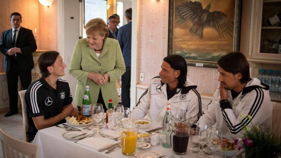 SJEFEN PÅ BESØK: Angela Merkel stakk innom gullfavorittene forleden. Her i en fotballprat med Mesut Özil, Tim Wiese og Sami Khedira (til høyre).. FOTO: EPA/Guido Bergmann.