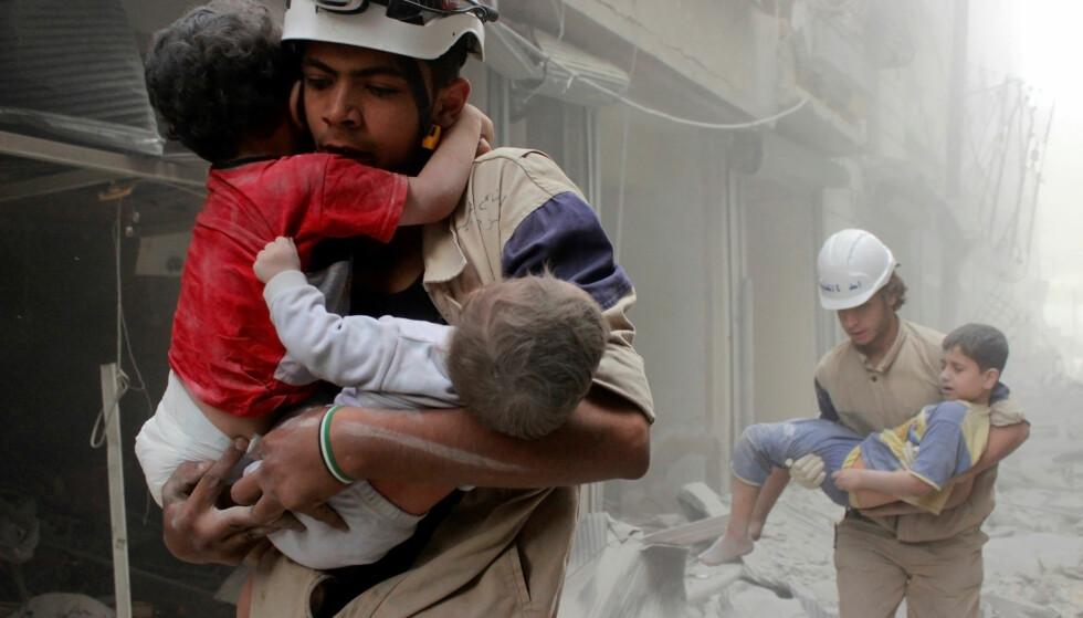 REDDET: Barn reddes ut etter et bombeangrep fra styrker alliert med president Bashar al-Assad. Foto: Sultan Kitaz/Reuters