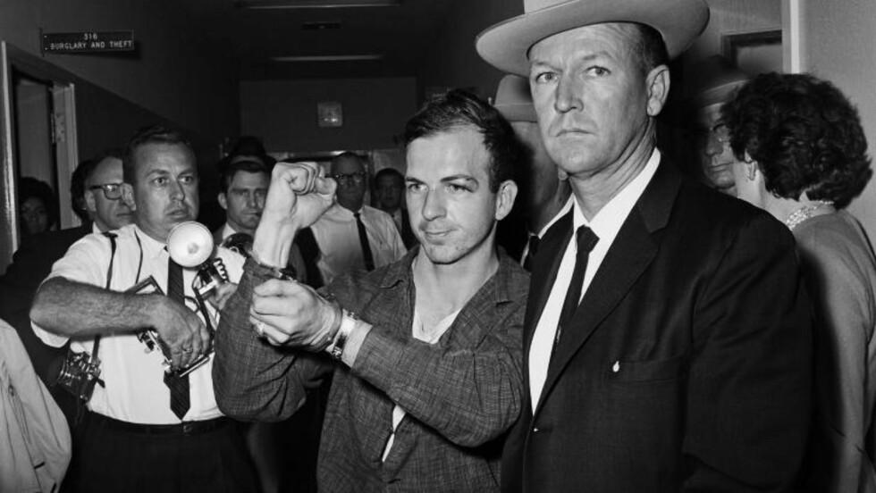 KNYTTET NEVE:  Lee Harvey Oswald knytter neven foran pressen etter å ha blitt arrestert for drapet på president John F. Kennedy. Arkivfoto: Tom Dillard/Scanpix
