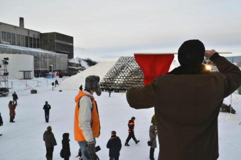 LEDET MASSENE: Arirang-instruktøren Ri Gwang Nam dirigerte det levende bildet fra en snøhaug til høyre for snøtribunen. Foto: Bjørn S. Kristiansen