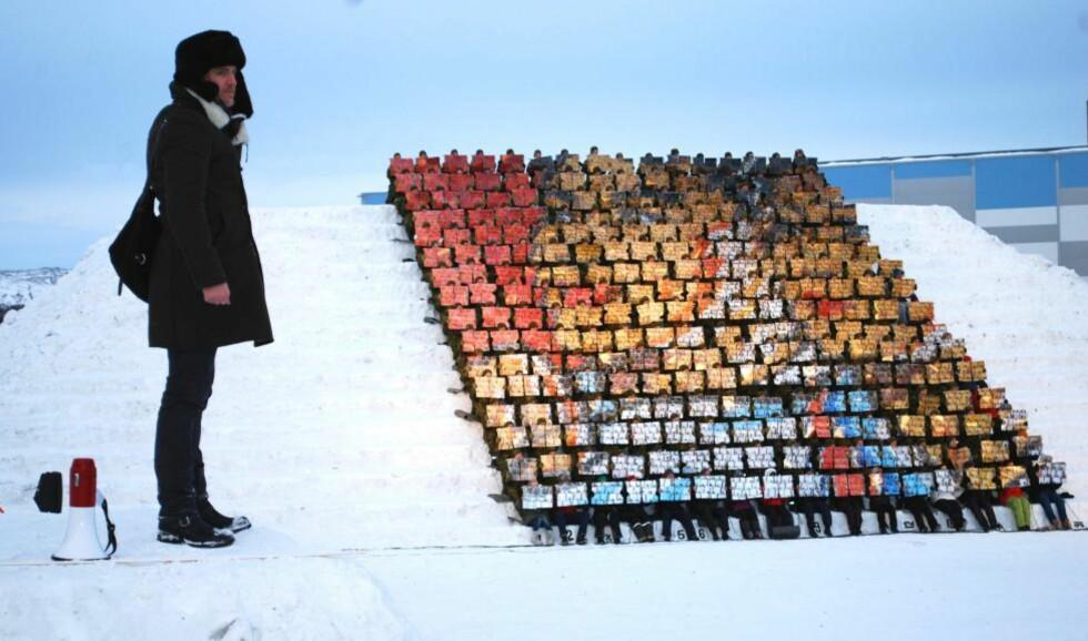 LEVENDE BILDE: På en høyde overfor Kirkenes, var det bygget en snøtribune, og to utsiktsplatåer. På den ene sto kunster Morten Traavik, på den andre sto de nordkoreanske instruktørene som under stram regi har forvandlet 256 nordmenn til ett, stort levende bilde. Foto: Bjørn S. Kristiansen