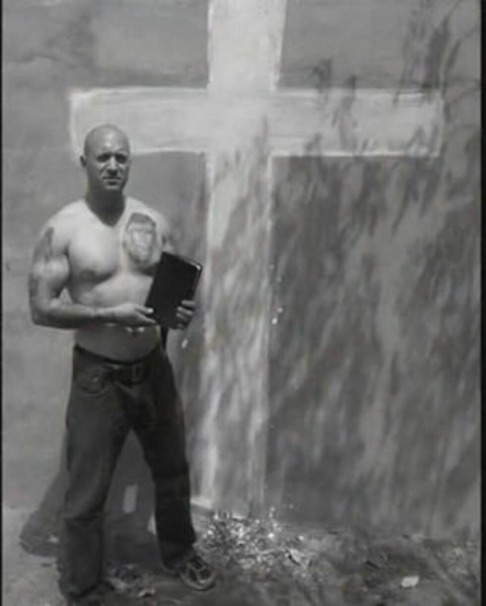 POSERER: Nick Greger foran et kors i en video han nylig har publisert på Youtube. Foto: Privat/Fra video