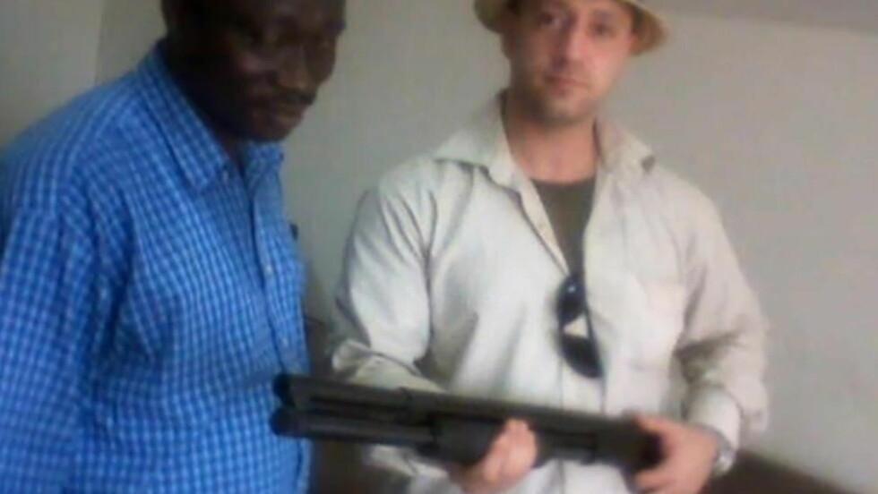 VÅPEN: Nick Greger poserer med ei hagle under et besøk i Afrika, trolig i Kongo. Foto: Privat/Fra video