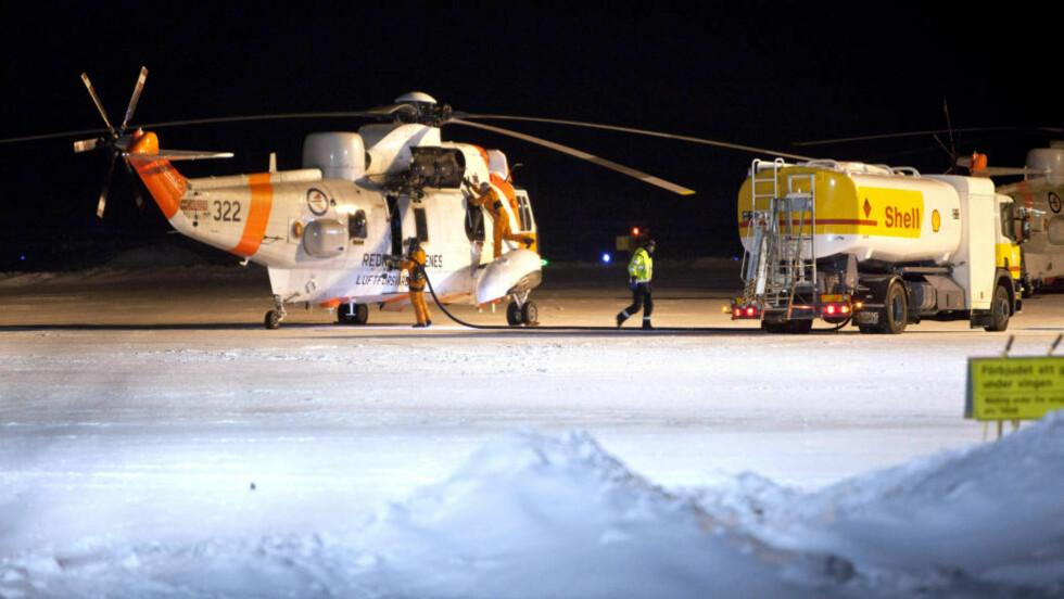 MÅTTE SNU: To norske Sea King redningshelikoptre måtte i kveld snu på grunn av dårlig vær. Helikoptrene var i utgangspunktet med i letingen etter det savnede Hercules-flyet. Her er Sea King-helikopteret på flyplassen i Kiruna torsdag kveld. Foto: Fredric Alm / Scanpix