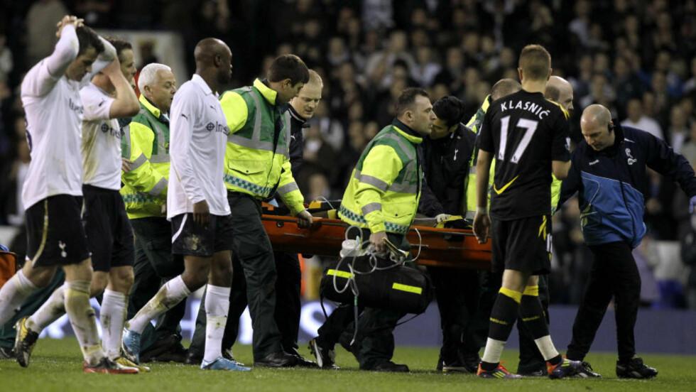 FRAKTES AV BANEN: Fabrice Muamba blir fraktet av banen etter at han ble liggende bevisstløs på banen i kampen mellom Bolton og Tottenham. Kampen ble avlyst rett etterpå. Foto: AP Photo/Matt Dunham