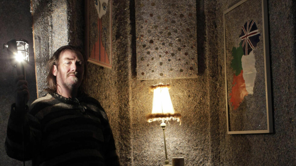 LEILIGHET LAGET AV PENGER: Kunstneren Frank Buckley (50) poserer i huset som er laget av 1,4 milliarder euro. Murstein av utgåtte eurosedler er brukt i vegger, gulv og tak. Foto: Cathal McNaughton / REUTERS / SCANPIX
