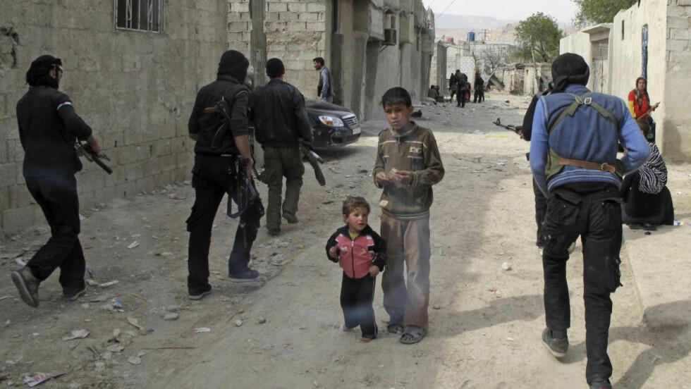 - VIL ALDRI SLÅ REGIMET: Russlands utenriksminister mener opposisjonen aldri vil klare å seire over Bashir al-Assads hær - selv om man væpner dem til tenna. Her går opposisjonskrigerne gjennom et nabolag i Damaskus i Syria. Foto: AP Photo/Scanpix