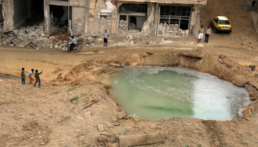 ENORME SKADER: Bombardementet mot den østlige delen av Aleppo synes å være uten stans. Her er et hull i bakken blitt fyllt med vann på et sted skadd av bombingen i den opprørskontrollerte delen av Aleppo. Foto: REUTERS/Abdalrhman Ismail