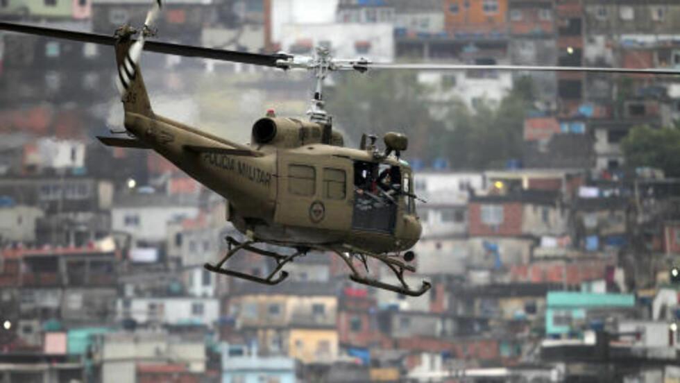 HOLDT OPPSYN: Politihelikopteret, fullt av tungt bevæpnet personell, overvåket aksjonen i dag. Foto: AFP/Luiza Castro/Scanpix