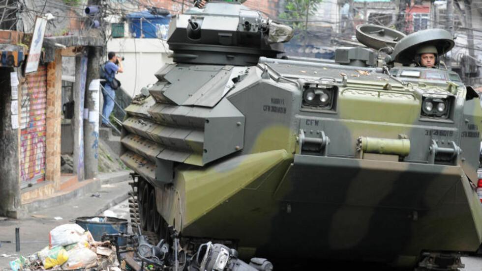 KNUSTE SEG VEI: En av politiets panservogner brøyter seg vei gjennom søppel og skur. Etter 30 år har nå politiet kontroll over Rosinha-favelaen. Flere fotografer var til stede for å forevige raidet. Foto: AFP/Antonio Scorza/Scanpix