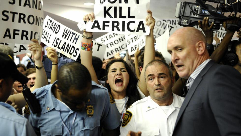 PROTESTERTE: Hundrevis av mennesker demonstrerte i lokalene der klimaforhandlingene foregikk i Durban, fredag 9. desember.  Foto: AFP PHOTO / STEPHANE DE SAKUTIN/ SCANPIX.