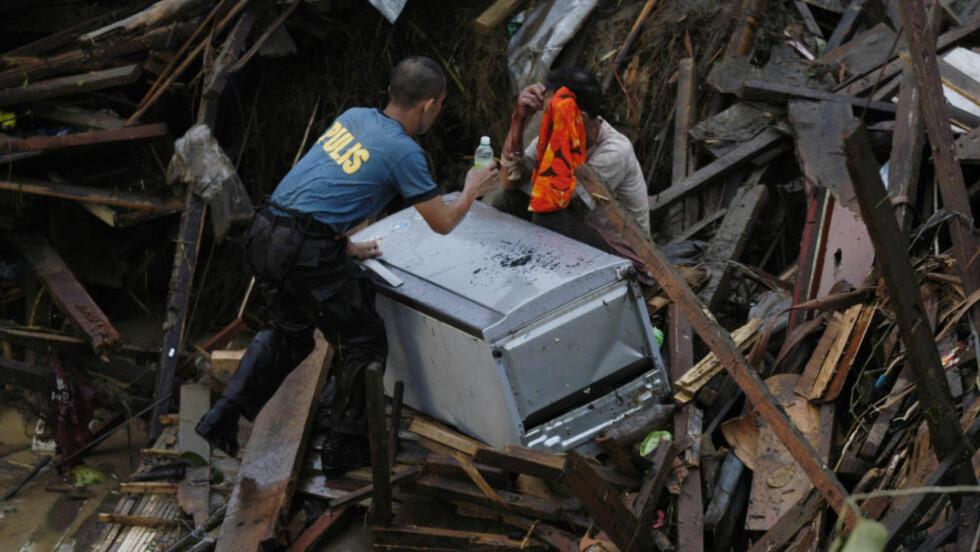 RASERT:  Husene er fullstendig smadret i denne bydelen utenfor Oro City på Filippinene. En redningsmann hjelper en beboer, som har funnet kjøleskapet i vrakrestene av boligen.FOTO: Froilan Gallardo, AP/SCANPIX.