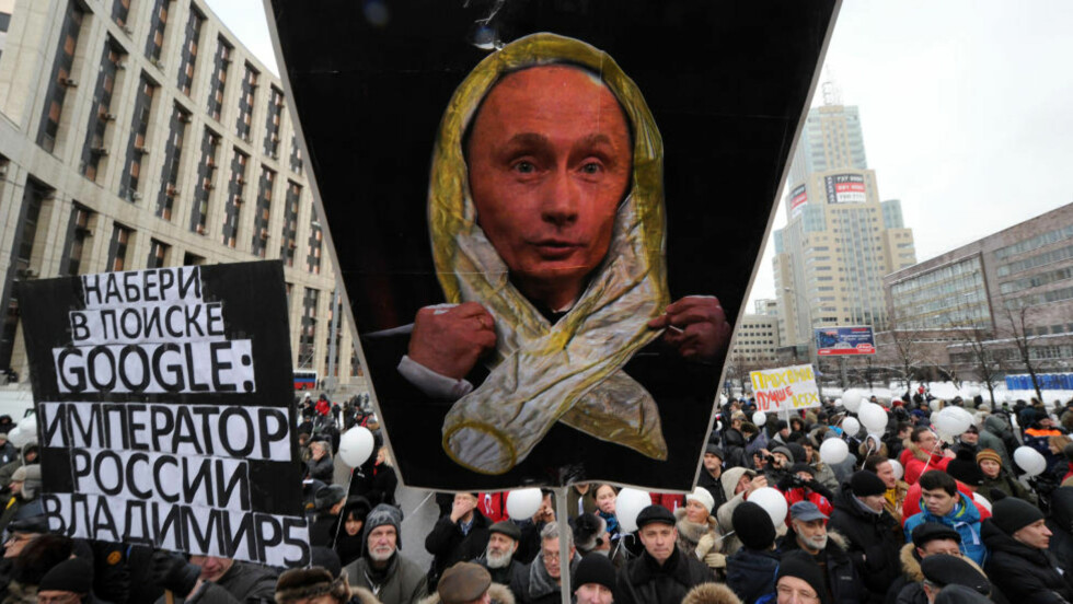 GJØR NARR AV PUTIN: 120 000 mennesker protesterer i dag i Moskvas gater mot det omfattende jukset under parlamentsvalget tidligere i desember. Noen av demonstrantene er utstyrt med plakater som viser Putin iført en kondom som et hodeplagg eller sjal, etter hans sleivete kondombemerkning Foto: AFP PHOTO/SCANPIX