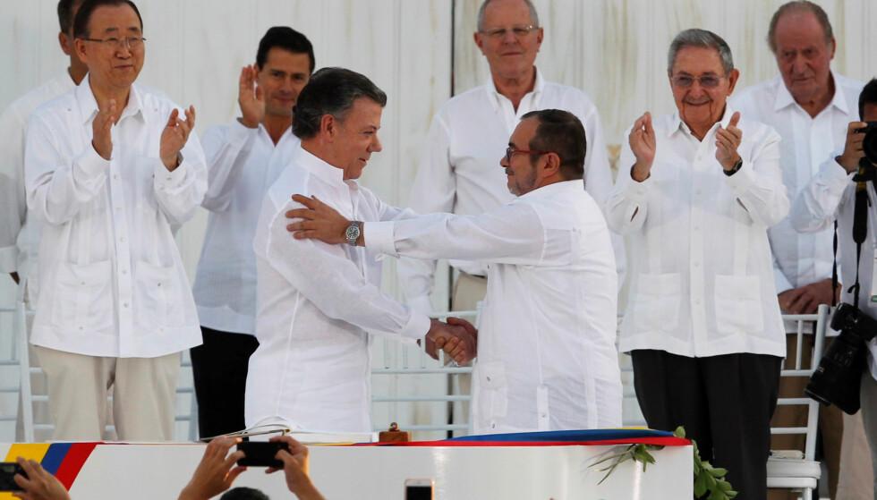 ETTER 52 ÅR: Colombias president Manuel Santos (til venstre) og leder for den marxistiske FARC-geriljaen, gir hverandre hånden etter å ha signert fredsavtalen mandag. Foto: John Vizcaino, Reuters/NTB Scanpix.