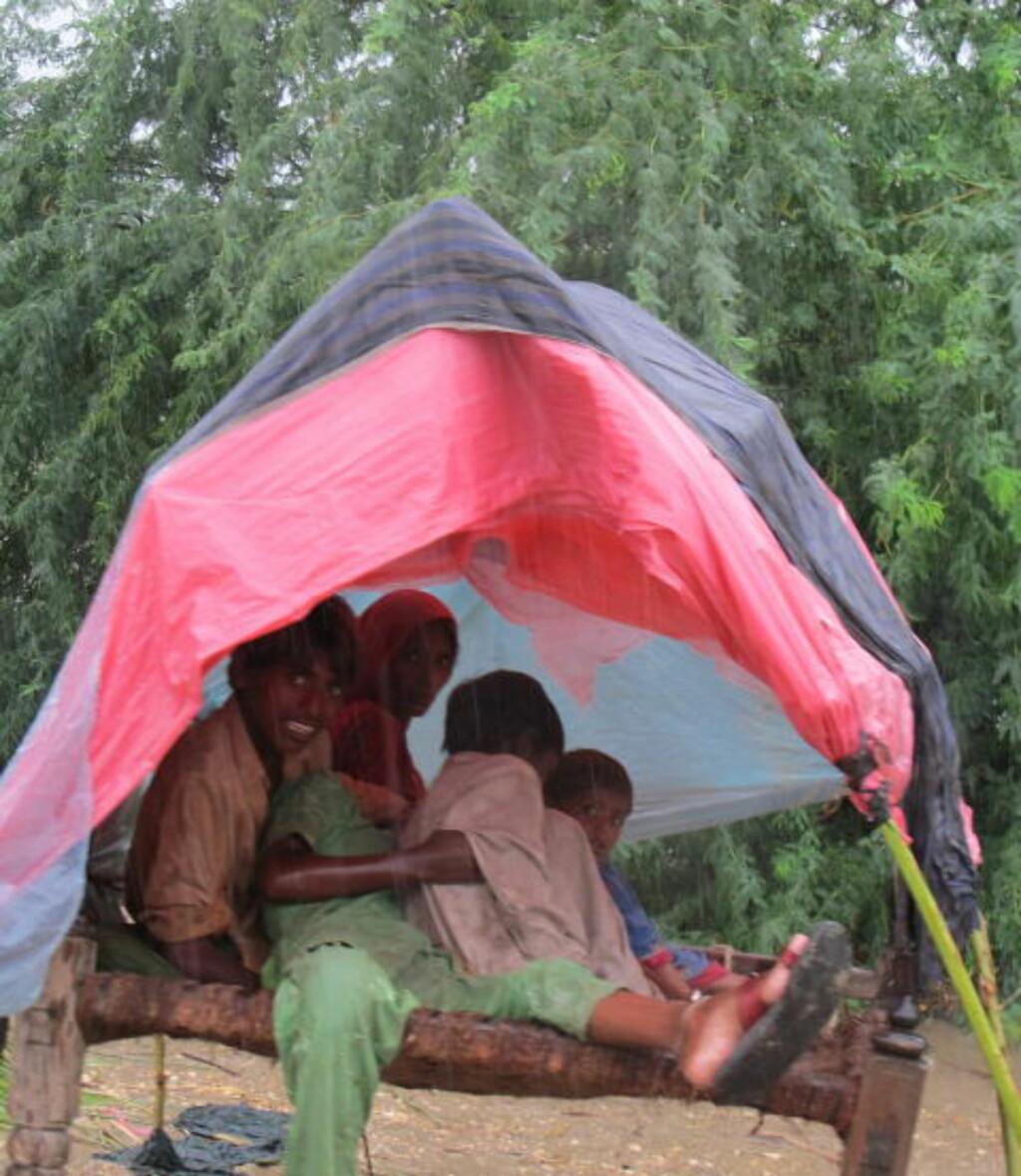NØD: En familie søker ly for regnet etter at huset deres er skylt bort av vannmassene. Totalt er 1,2 millioner hus ødelagt, 1,8 millioner mål med jord under vann og 300 000 mennesker er hjemløse. Foto: Mohammad Naeem/Kirkens Nødhjelp