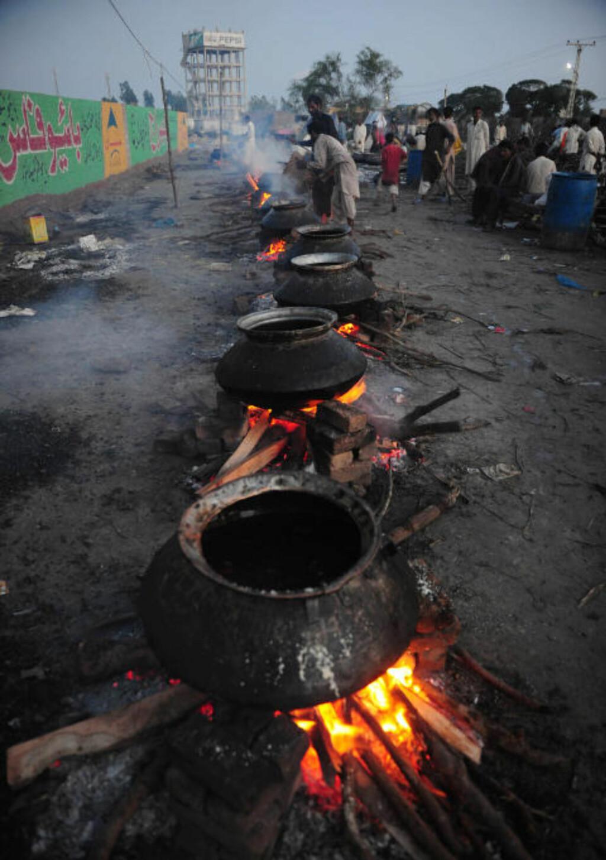 MATKØ: De flomrammede i byen Badin blir servert mat. Disse menneskene er blant de «heldige», ute på landsbygda er forholdene langt verre. Foto: Asif HASSAN/AFP/Scanpix