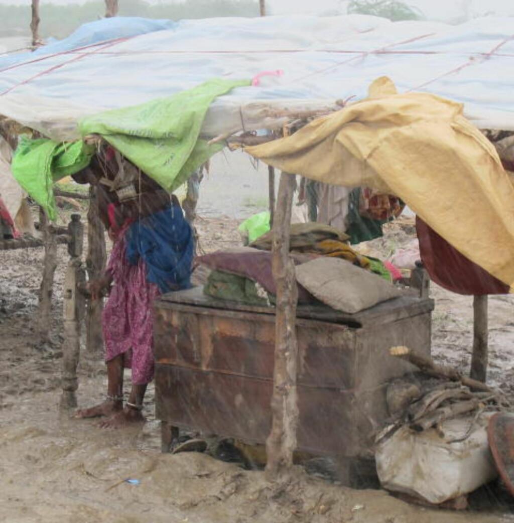 REGN, REGN, REGN: Regnet strømmer fortsatt ned, denne kvinnen har søkt tilflukt under et provisorisk telt, men bakken er bare gjørme. Foto: Mohammad Naeem/Kirkens Nødhjelp
