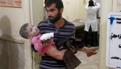 REDDET: En syrisk pappa bærer inn sønnen sin til et av de provisoriske helsestedene i Øst-Aleppo etter at familiens hus ble bombet. Begge er heldige - som overlevde. Nær 200 personer mistet livet i helga. Foto: Jawad al Rifai / Anadolu Agency / Scanpix
