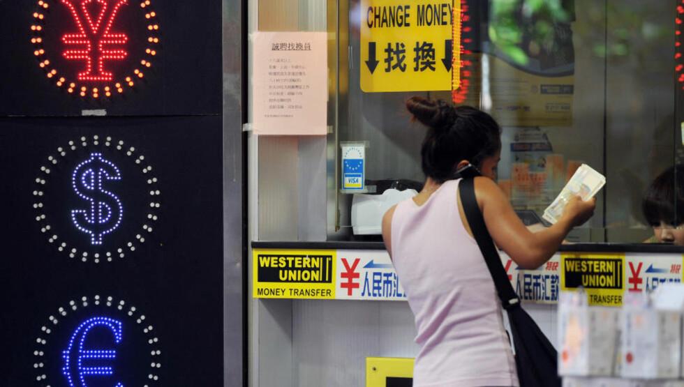 Nødvendig: En kvinne veksler penger i Hong Kong. «Dersom man ikke har kontanter å falle tilbake på, finnes det ingen måte å kunne garantere at mennesker får handlet nødvendigheter som mat», skriver kronikkforfatteren. Illustrasjonsfoto: Laurent Fievet/AFP/Scanpix