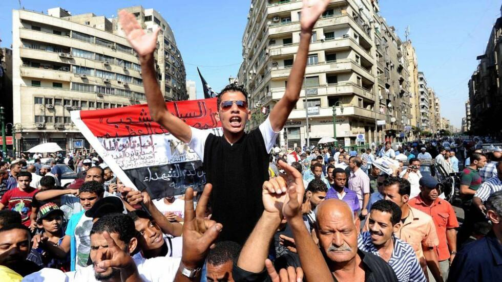 TAHRIR-PLASSEN: Knutepunktet i sentrum av Kairo, øst for Nilen. Vest for Tahrir starter løvebroen Qasr el Nil som forbinder Cairos østbredde med vestbredden. Mellom broen og Tahrir ligger hovedkvarteret til den Arabiske liga. Sør for Tahrir står Mogamma, regjeringens administrative bygning, kalt «byråkratiets uendelige labyrint». I vest ligger det Amerikanske Universitetet i Cairo og nord for Tahrir det berømte egyptiske museum. Like ved siden av ligger bygningen til det nasjonaldemokratiske parti, i dag et utbrent symbol over et diktatorisk enevelde. Foto: EPA/MOHAMED OMAR