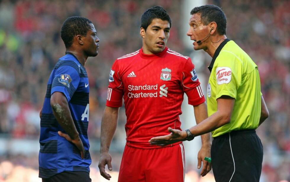 RASISTISKE ROP?:  Liverpools Luis Suarez blir anklaget av Patrice Evra for å ha kommet med rasistiske rop til ham underveis i kampen. Her står de sammen med dommer Andre Marriner. Foto: EPA/LINDSEY PARNABY