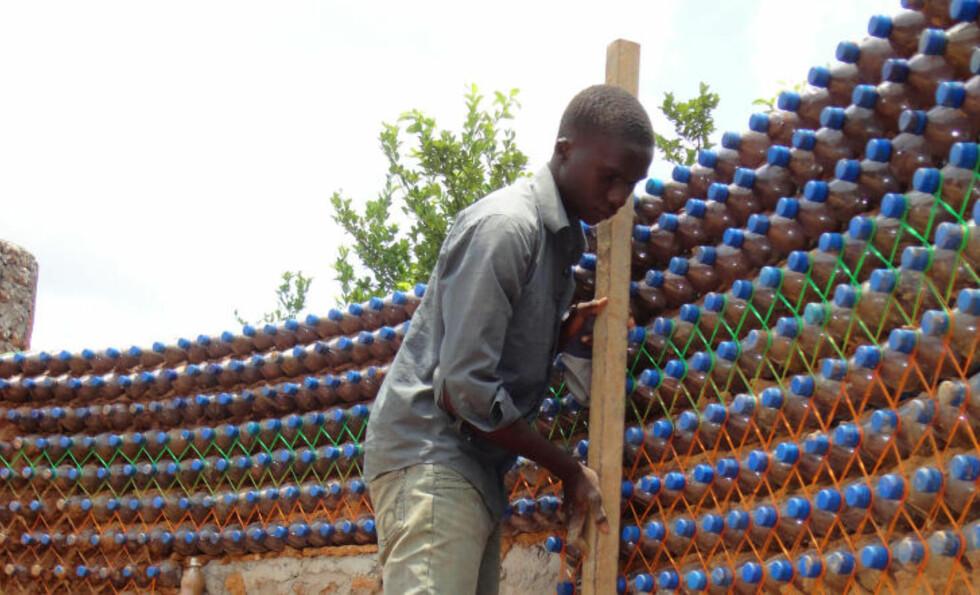 STERKERE ENN MURSTEIN:  Flaskene legges oppå hverandre, og det legges sement imellom. Konstruksjonen hevdes å være sterkere enn murhus. Foto: AFP PHOTO / Aminu ABUBAKAR / Scanpix