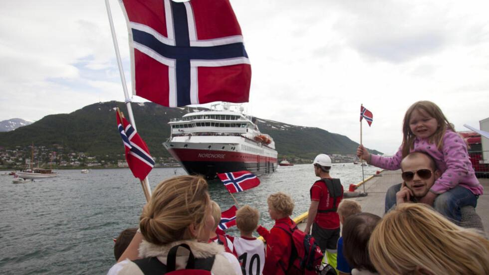 FOLKEFEST: Nordmenn elsker en folkefest. Her står tromsøværingene klare med norske flagg for å heie på MS Nordnorge. Foto: Jan Morten Bjørnbakk / SCANPIX