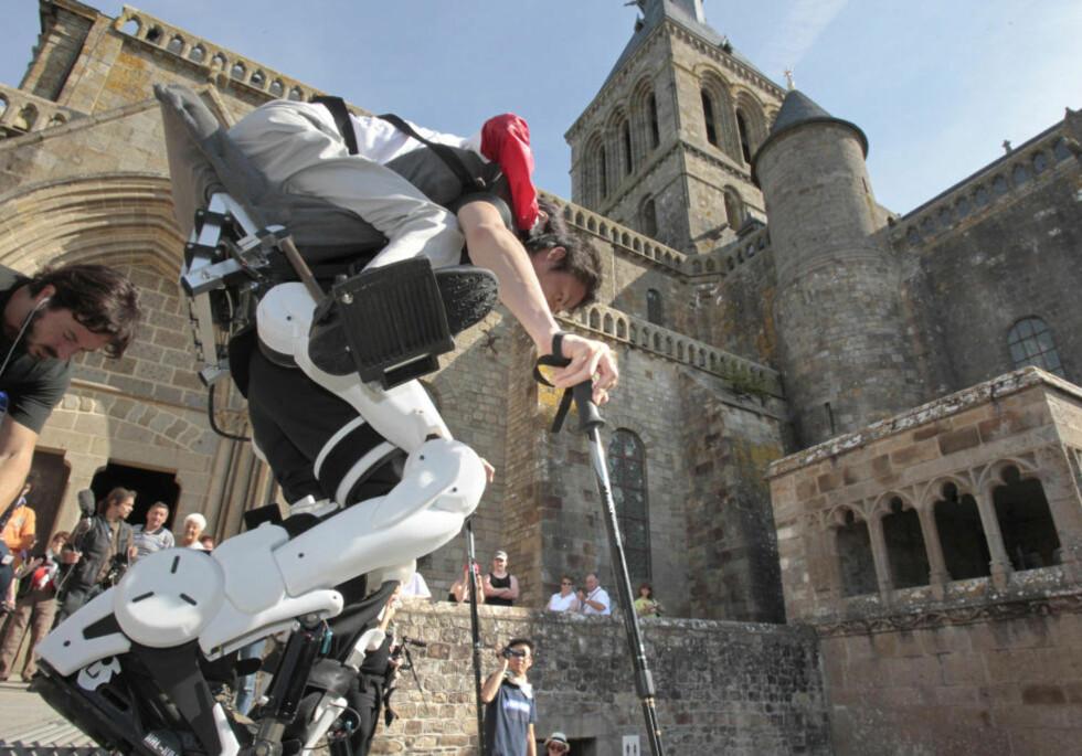«CYBERMENNESKE»: Robotdrakta gjør at Hirosama Hara enkelt kan bære lamme Seiji Uchida opp landetmerket i Normandie. Foto: AFP PHOTO KENZO TRIBOUILLARD/SCANPIX