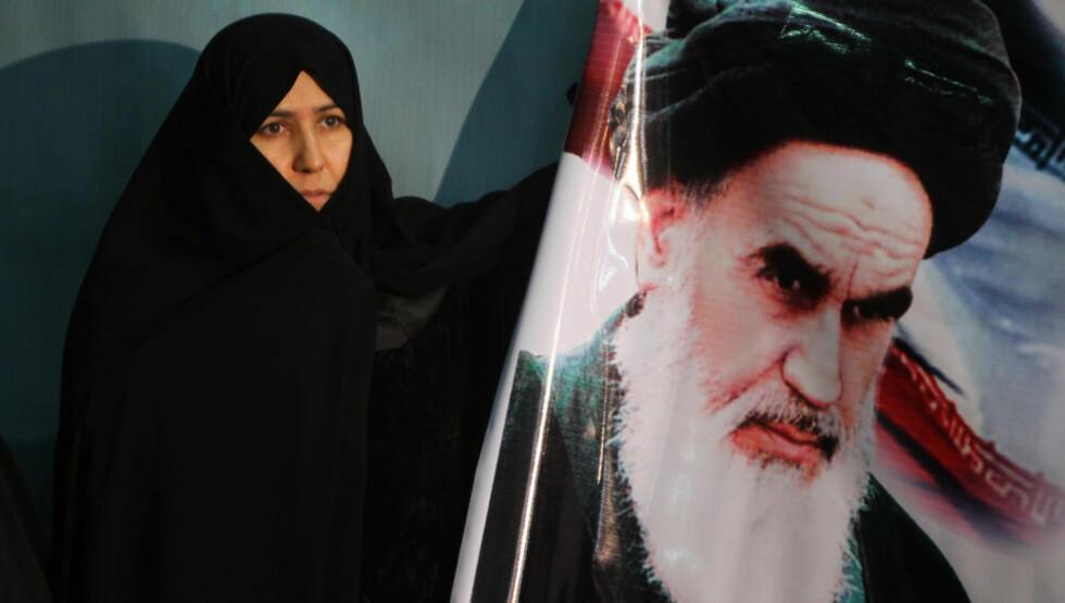 TERRORISTENS LIKE?  En iransk kvinne med en plakat av Ayatollah Khomeini. «Breiviks ideal er et patriarkalsk og autoritært Europa, i siste instans styrt av e selvbestaltet elite», skriver kronikkforfatteren. Foto: Atta Kenare /AFP/Scanpix