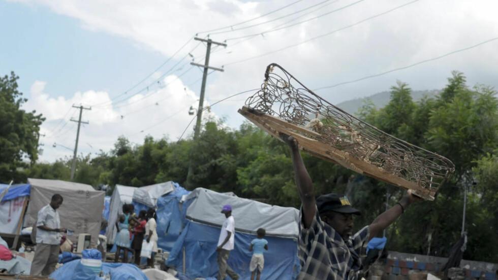 TRUES AV STORM: En mann som er blitt bortvist fra en teltleir bærer en treseng i Port-au-Prince 18. juli. Over 600.000 mennesker bor fortsatt i telt etter fjorårets jordskjelv. Nå truer stormen Emiliy med styrtflod og jordras. Foto: REUTERS / Swoan Parker / SCANPIX