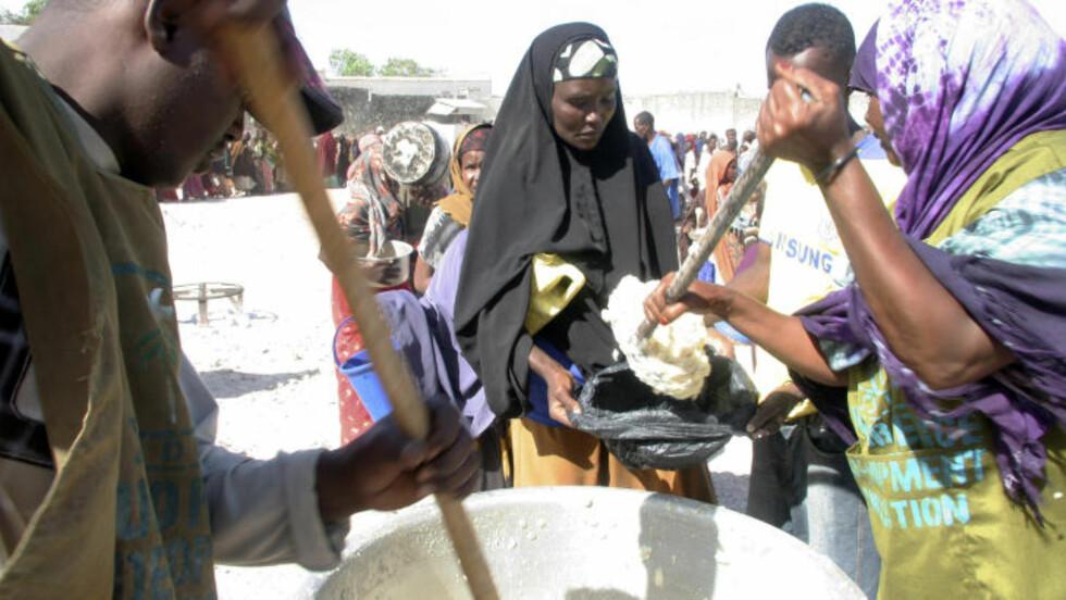 FÅR MAT: Halima Yusuf, som er mor til åtte, står i kø for å få dagens porsjon med mat fra World Food Programme i Mogadishu. Foto: AP Photo/Katharine Houreld
