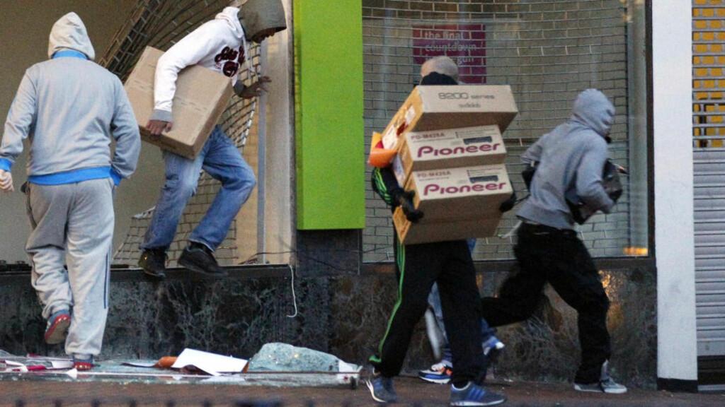 PLYNDRER: Når ansiktene på mobben nå kommer fren viser det seg at det slettes ikke bare er sint, fattig ungdom som står bak opptøyene. Foto: REUTERS/Darren Staples
