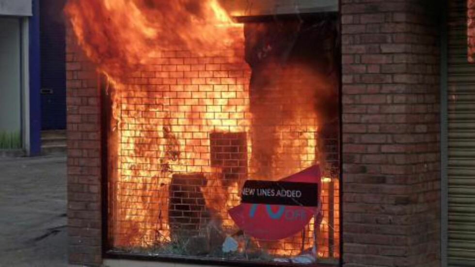 I BRANN: En butikk i Manchester er satt fyr på av pøbler. Foto: EPA/Dave Thompson/Scanpix