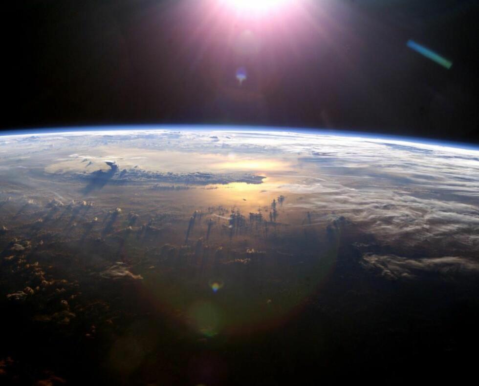 """LIV OG DØD: Sola skinner ikke bare livgivende lys, men også destruktivt. UV-stråling kan føre til alt fra solbrenthet til hudkreft og alvorlige øyeskader, men blir heldigvis i stor grad absorbert av ozonlaget i stratosfæren. I vinter har imidlertid dette beskyttende sjiktet, populært kalt """"jordas solbrille"""", vært rekordtynt over Arktis. Bildet viser en soloppgang som sett fra Den internasjonale romstasjonen ISS. Foto: NASA"""
