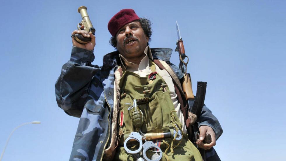 ET TEATER: Mange av de libyske «opprørerne» har ikke en gang vært ved fronten. Mange kjører bare rundt i biler, veiver med flagg og skyter ut i løse lufta. De fleste mangler våpenkunnskap og ledelsen er kaotisk. Her poserer en opprører i nærheten av byen Ajdabiya. Foto: AFP/ARIS MESSINIS
