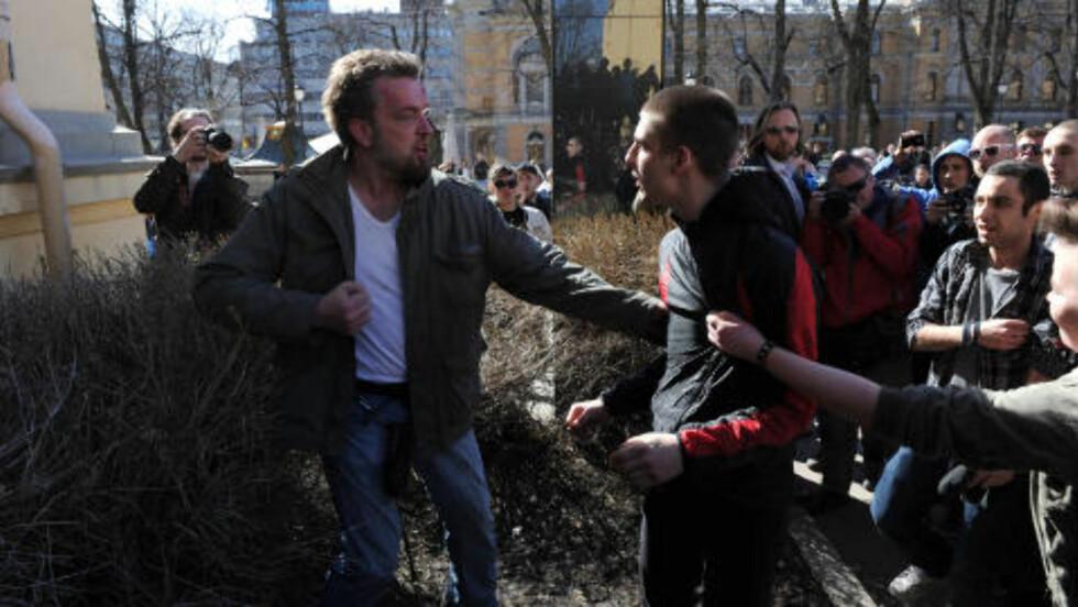 BLØDENDE: Mannen til venstre beskyldes av demonstrantene for å ha slått ned ei jente. Han ble raskt overmannet og gitt juling, noe blødende sår i panna tydelig viser. Foto: Øistein Norum Monsen / Dagbladet