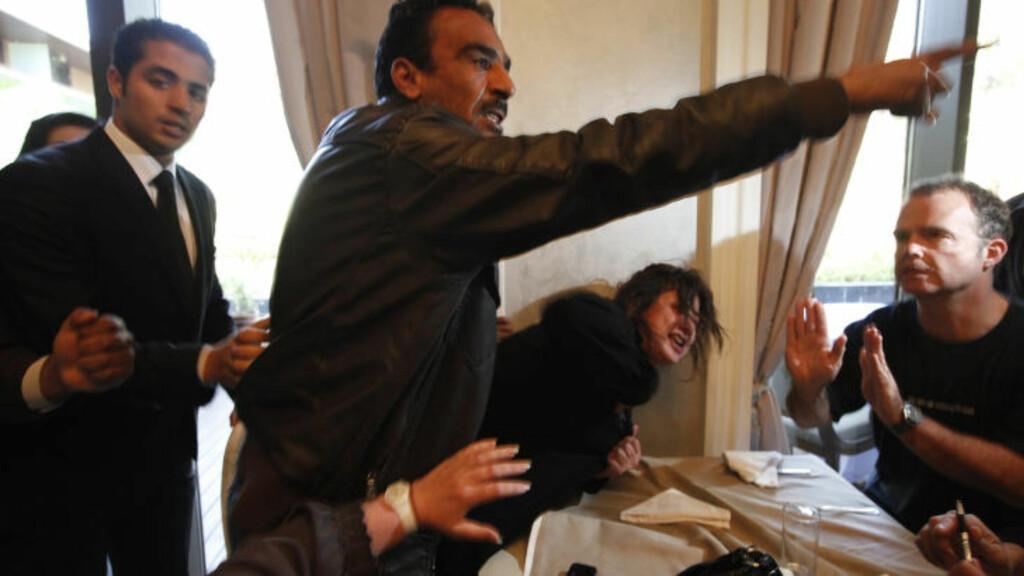 PÅGREPET: Eman al-Obaidi løp inn på pressekonferansen med de utenlandske journalistene, men ble stanset av sikkerhetsvakter.  Foto: REUTERS/Zohra Bensemra/Scanpix