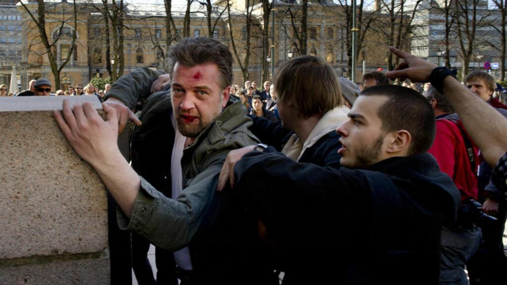 SAMMENSTØT: Her blir Erik Glømmi forsøkt fjernet fra Universitetsplassen etter å ha blitt utsatt for vold. . Foto: Øistein Norum Monsen /DAGBLADET