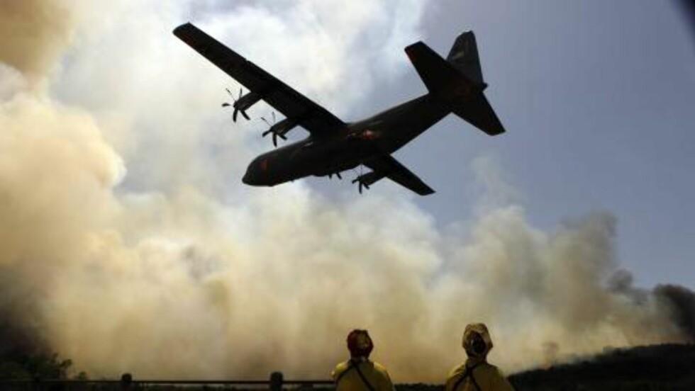 SLUKNINGSARBEIDET: Brannmenn står og ser på at et fly som skal hjelpe dem med slukningsarbeidet nær Possum Kingdom i Texas. Foto: Scanpix/AP Photo/LM Otero