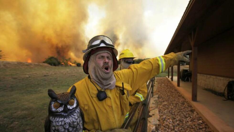 PRØVER Å REDDE HJEM: Brannmann Craig Howard roper til sine kolleger når de kjemper for å redde et hus bra brannen. Foto: Scanpix/AP Photo/LM Otero