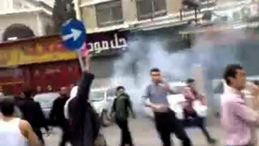ANGREPET: Demonstranter som angivelig løper i dekning etter å ha blitt beskutt av tåregassgranater i Damaskus i Syria. Bildet er tatt fra en video på Youtube og innholdet er derfor ikke uavhengig bekreftet. Foto: AFP PHOTO/YOUTUBE/SCANPIX