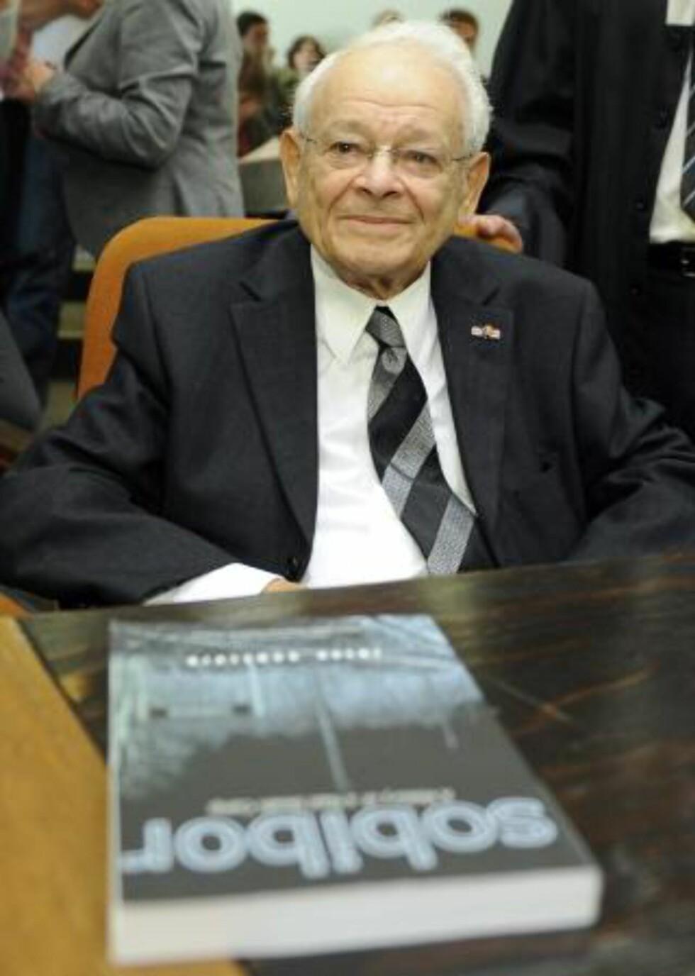 MISTET FAMILIEN: Jules Schelvis (90) mistet familien sin under holocaust, men overlevde selv nazistenes utryddelsesleirer. Han er en av dem som brakte saken mot Demjanjuk inn for tysk rett, og sitter her i rettssalen i dag, med sin bok «Sobibor». Foto: TOBIAS HASE/EPA/SCANPIX
