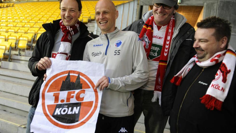 GLAD: Ståle Solbakken ble overrasket av Köln-supportere etter gårsdagens FC København-kamp. Her poserer han med klubblogoen til sin nye klubb. Foto: AFP PHOTO/ CLAUS FISKER/Scanpix