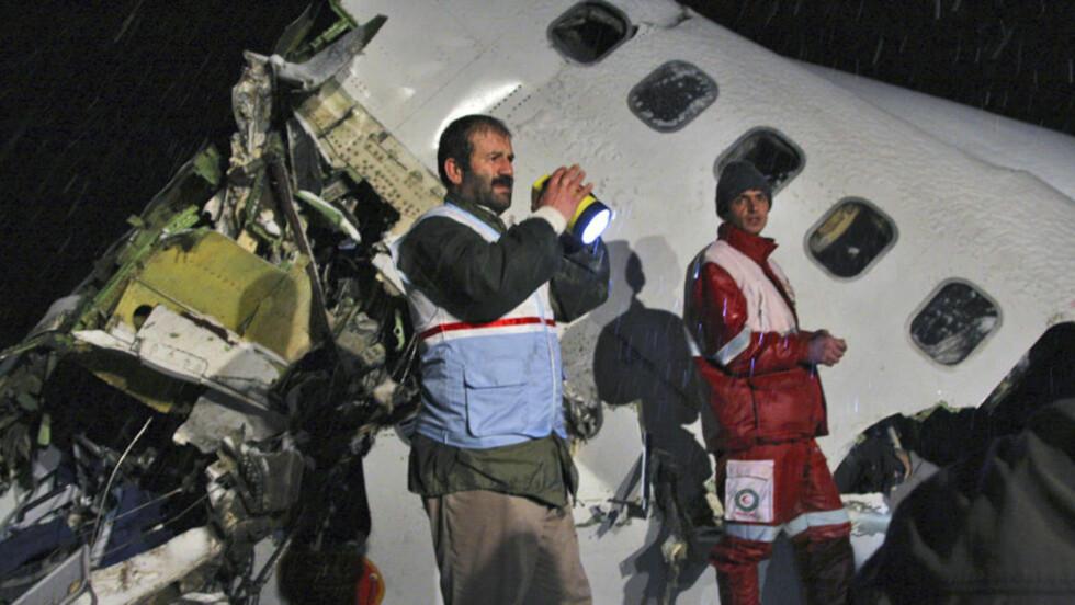 MINST 77 DREPT: Redningsmannskapene på stedet har et tungt arbeid etter flystyrten i Iran i går. Foto: AP/Mehr News Agency, Esfandiar Asgharkhani/Scanpix