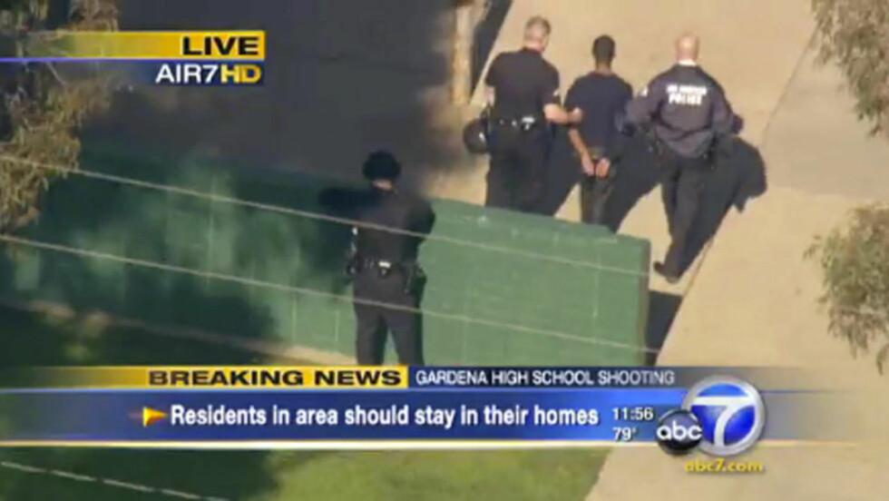 PÅGREPET: Den antatte gjerningsmannen blir her ført bort fra skolen. Foto: AP Photo/ABC7.com/Reuters/Scanpix
