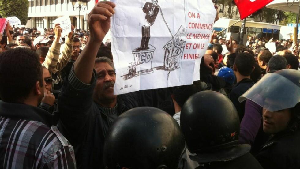 GIR OSS IKKE NÅ: Langt flere mennesker var ute i gatene og demonstrerte i Tunis' gater i dag enn tidligere. De vet hva de vil:«Vi har begynt oppryddinga og vi holder på til vi er ferdige», som det står på plakaten denne demonstranten holder. Foto: Jacques Hvistendahl/Dagbladet