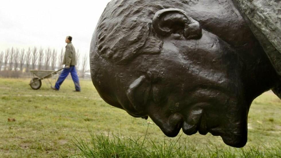 LENIN ER FORTSATT MED: Preger han fortsatt norsk venstreside? Her ligger en henslengt Lenin ingen lenger har bruk for i en bakhage i Romania. Statuen pleide å stå i hovedgata i hovedstaden. Foto: AP/Vadim Ghirda